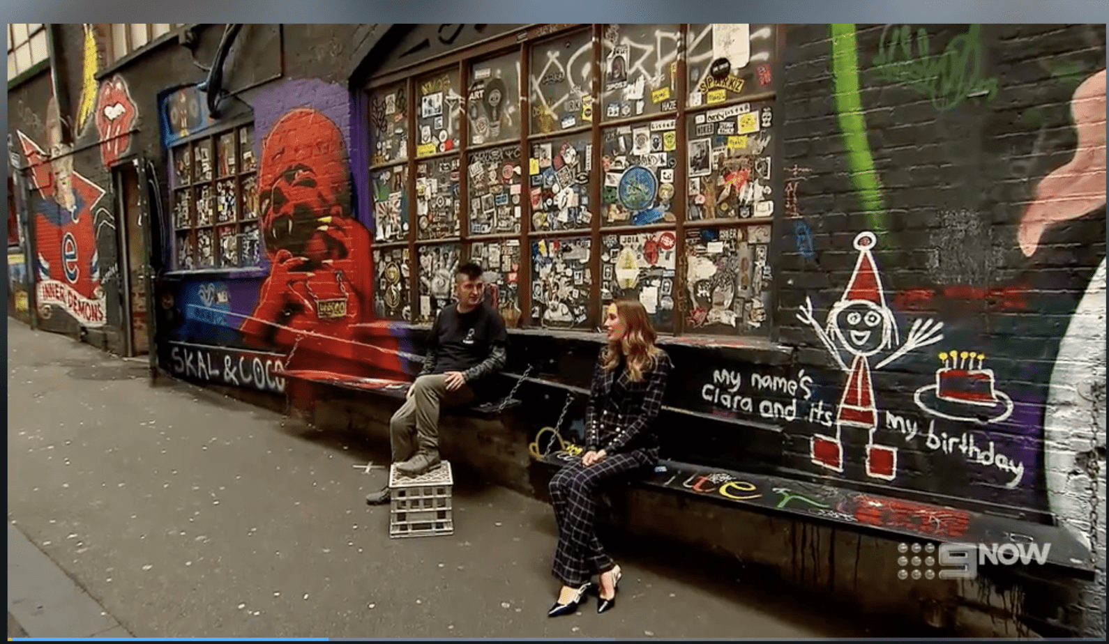 Man and woman in Melbourne Laneway talking about street art.